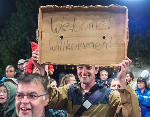 "In this Saturday, Sept. 5, 2015 file photo, a man holds a ""Welcome"" sign during the arrival of refugees at the train station in Saalfeld, central Germany. Hundreds of refugees arrived in a train from Munich to be transported by busses to an accomodation"