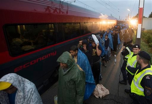In this Saturday morning, Sept. 5, 2015 file photo, migrants board a train after arriving at the border station between Hegyeshalom, Hungary, and Nickelsdorf, Austria. Hundreds of migrants came from Budapest as Austria in the early-morning hours said it a