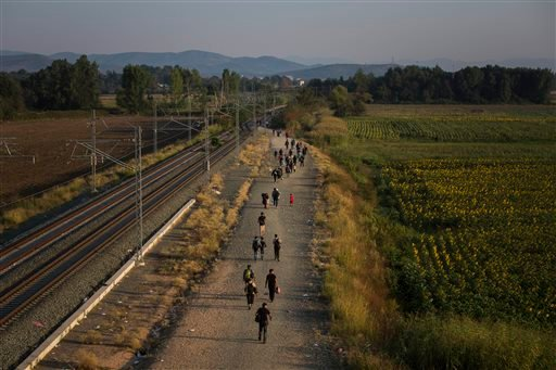 In this Thursday Aug. 27, 2015 file photo, migrants walk alongside railway tracks at Idomeni, northern Greece to cross the border and enter Macedonia. In the 28-nation EU, some countries have sought to block the unprecedented flow of migrants fleeing war