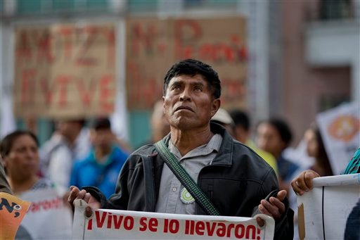 "In this March 10, 2015 file photo a demonstrator carries a sign that reads in Spanish: ""They took them alive, return them alive,"" in reference to 43 missing students from the Ayotzinapa rural teachers college, during a march in Mexico City. An independent"