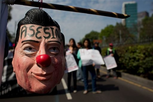 "In this Jan. 26, 2015 file photo a protestor carries a hanging mask of Mexican President Enrique Pena Nieto marked with the word in Spanish ""Assassin"" during a march in Mexico City. An independent report released Sunday Sept. 6, 2015 dismantles the Mexic"