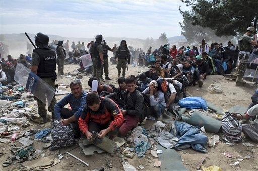 Refugees and migrants wait to cross the border from the northern Greek village of Idomeni to southern Macedonia, Monday, Sept. 7, 2015. Greece has borne the brunt of a massive refugee and migration flow of people heading into the European Union. (AP Photo