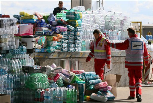 Red Cross workers look at aid goods for migrants at the border between Hungary and Austria, in Nickelsdorf, Austria, Monday, Sept. 7, 2015. (AP Photo/Ronald Zak)