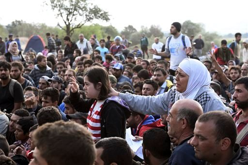 Refugees and migrants wait to pass the borders from the northern Greek village of Idomeni, to southern Macedonia, Monday, Sept. 7, 2015. The country has borne the brunt of a massive refugee and migration flow of people heading into the European Union. (AP