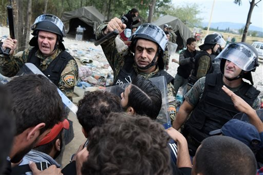 Macedonian policemen scuffle with refugees and migrants as they wait to pass the borders from the northern Greek village of Idomeni, to southern Macedonia, Monday, Sept. 7, 2015. The country has borne the brunt of a massive refugee and migration flow of p