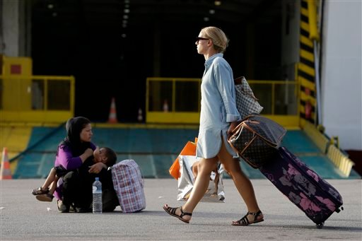 A traveler passes next to an Afghan woman who breastfeeds her baby at the Athens' port of Piraeus on Monday, Sept. 7, 2015. About 2,500 refugees and migrants arrived with the ferry Eleftherios Venizelos as Frontex, the EU border agency, says more than 340