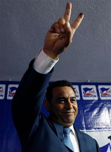 Television comedian and presidential candidate for the National Front of Convergence party Jimmy Morales, flashes the V sign for photographers during a press conference at his party headquarters in Guatemala City, Sunday, Sept. 6, 2015. Guatemalans headed