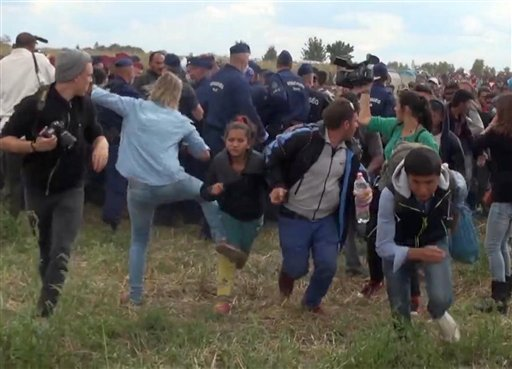 In this image taken from TV a Hungarian camerawoman, center left in blue, kicks out at a young migrant who had just crossed the border from Serbia near Roszke Hungary Tuesday Sept. 8, 2015. The camerawoman has been fired after she was caught on video kick