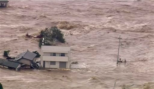 In this photo taken from video provided by Japan's Tokyo Broadcasting System (TBS) television network, a man, right, stands stranded in the middle of raging floodwaters before being rescued by a military helicopter in Joso, Ibaraki prefecture.