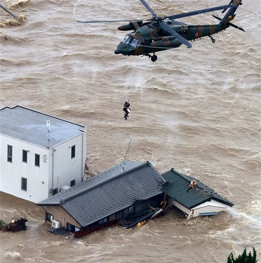 A resident is rescued from a flooded residential area in Joso, Ibaraki prefecture, northeast of Tokyo Thursday, Sept. 10, 2015.