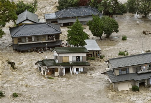 People inside houses wait to be rescued as the houses are submerged in water flooded from a river in Joso, Ibaraki prefecture, northeast of Tokyo Thursday, Sept. 10, 2015.