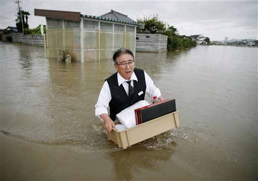 A man carries belongings through a flooded street in Oyama, Tochigi prefecture, northeast of Tokyo Thursday, Sept. 10, 2015.