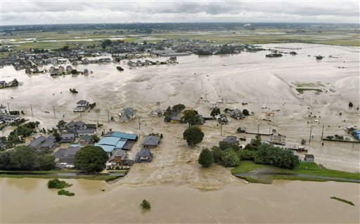Houses are submerged in water flooded from a river in Joso, Ibaraki prefecture, northeast of Tokyo Thursday, Sept. 10, 2015.