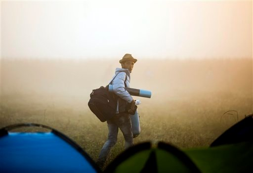 A migrant leaves the camp and walks through a field to avoid checkpoints along the railway tracks connecting Horgos and Szeged near Roszke,Hungary , at the border between Hungary and Serbia, Sunday, Sept. 13, 2015. (Balazs Mohai/MTI via AP)