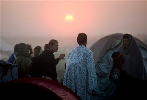 Migrants gather in their camp in Roszke, Hungary, at the border between Hungary and Serbia, Sunday, Sept. 13, 2015. (Balazs Mohai/MTI via AP)
