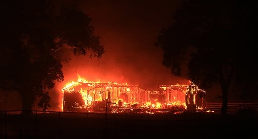 A home burns along Highway 29 in Hidden Valley,during the Valley fire, Saturday Sept. 12, 2015. (Kent Porter/The Press Democrat via AP)