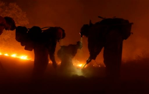 A California Department of Corrections and Rehabilitation inmate work crew builds a containment line ahead of flames from the Butte Fire, Saturday, Sept. 12, 2015 near San Andreas, Calif.(AP Photo/Rich Pedroncelli)