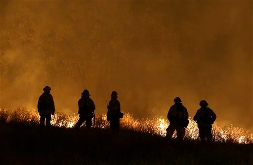 Firefighters stand guard as flames from the Butte Fire approach a containment line,Saturday, Sept. 12, 2015 in San Andreas, Calif.(AP Photo/Rich Pedroncelli)