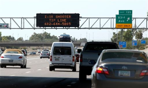 A sign still displays a shooter tip line above Interstate 10, Friday, Sept. 11, 2015, in Phoenix. Authorities have a person of interest in custody in a string of freeway shootings over the past two weeks and the man's white Chevrolet Tahoe, raising hopes