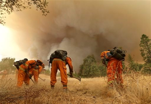 A California Department of Corrections and Rehabilitation inmate work crew builds a containment line ahead of a wildfire in Sheep Ranch, Calif., Sunday, Sept. 13, 2015. (AP Photo/Rich Pedroncelli)