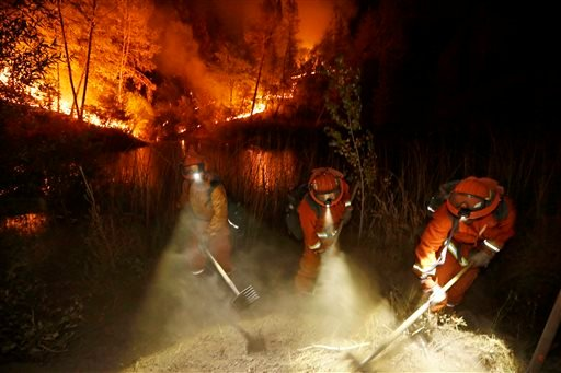 Firefighters create a firebreak near a home in Middletown, Calif., on Sunday, Sept. 13, 2015. (AP Photo/Elaine Thompson)