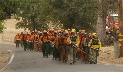 A California Department of Corrections and Rehabilitation inmate work crew walks through Sheep Ranch, Calif., on the way to battle a fire, Sunday, Sept. 13, 2015. (AP Photo/Rich Pedroncelli)