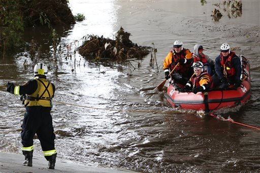 A swift-water rescue crew helps a man after he was stranded in a tree in the Los Angeles River near downtown Los Angeles on Tuesday, Sept. 15, 2015. Rescuers were looking for more victims possibly stuck in thick vegetation along the riverbank just north o