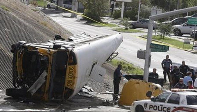 Investigators work around a Houston school bus, left, after it drove off a highway overpass, Tuesday, Sept. 15, 2015, in Houston, killing two students and seriously injuring three other people, police and school officials said. (AP Photo/Pat Sullivan)