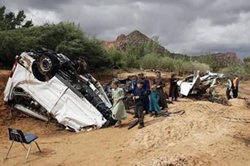 People walk pass damaged vehicles swept away during a flash flood Tuesday, Sept. 15, 2015, in Hildale, Utah. The floodwater swept away multiple vehicles in the Utah-Arizona border town, killing several people. (AP Photo/Rick Bowmer)