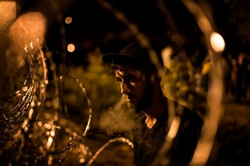 A Syrian refugee looks at Hungarian riot police from the Serbian side of the fence built by Hungarian authorities at the border between Serbia and Hungary, in Horgos, Serbia, Wednesday, Sept. 16, 2015. Events on the Serbia-Hungarian border where police te