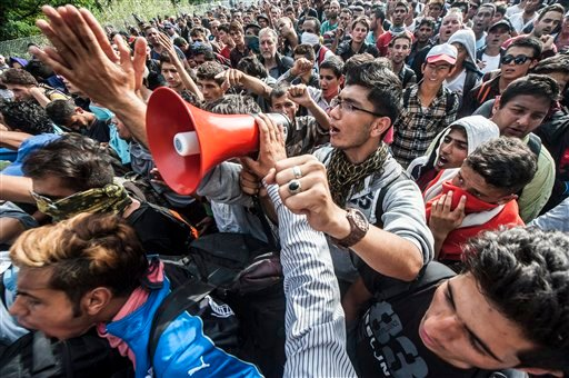 """Migrants demonstrate at the """"Horgos 2"""" border crossing into Hungary, near Horgos, Serbia, Wednesday, Sept. 16, 2015. Small groups of migrants continued to sneak into Hungary on Wednesday, a day after the country sealed its border with Serbia and began arr"""