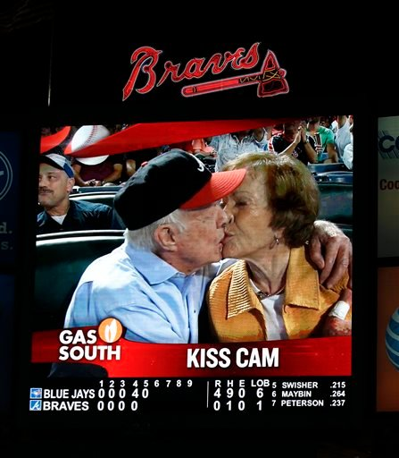 """Former President Jimmy Carter kisses his wife,Rosalynn, on the """"Kiss Cam"""" during a baseball game between the Atlanta Braves and the Toronto Blue Jays on Thursday, Sept. 17, 2015, in Atlanta."""