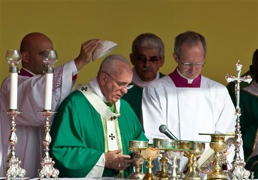 A priest places a skullcap on Pope Francis during Mass at Revolution Plaza in Havana, Cuba, Sunday Sept. 20, 2015. Pope Francis opens his first full day in Cuba on Sunday with what normally would be the culminating highlight of a papal visit: Mass before