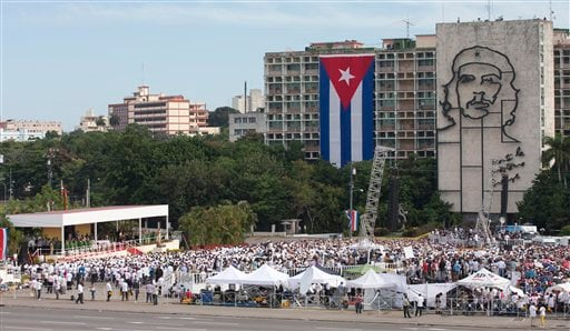 """People gather in Revolution Square as Pope Francis celebrates Mass in Havana, Cuba, Sunday, Sept. 20, 2015, where a sculpture of revolutionary hero Ernesto """"Che"""" Guevara and a Cuban flag decorate government buildings. Pope Francis opens his first full day"""