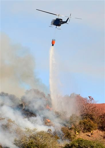 A helicopter drops water on a fire along Highway 68 east of Laureles Grade in rural Salinas, Calif., Saturday, Sept. 19, 2015. (David Royal/The Monterey County Herald via AP)