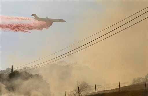 A plane drops fire retardant on a fire along Highway 68 east of Laureles Grade in rural Salinas, Calif., Saturday, Sept. 19, 2015. (David Royal/The Monterey County Herald via AP)