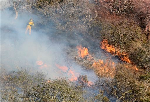Brush and oak trees flare up as firefighters work to contain a blaze that burns along Highway 68 east of Laureles Grade in rural Salinas, Calif., Saturday, Sept. 19, 2015. (David Royal/The Monterey County Herald via AP)