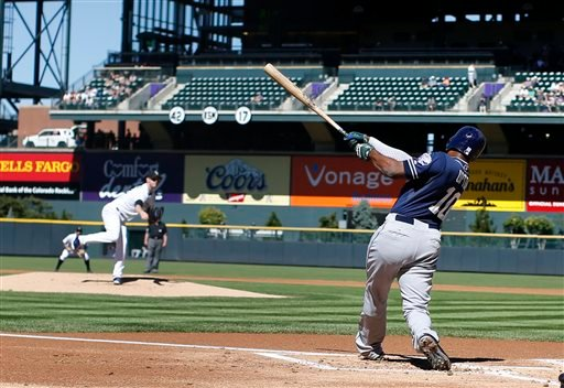 San Diego Padres' Justin Upton, front, flies out on a pitch from Colorado Rockies starting pitcher Kyle Kendrick in the first inning of a baseball game Sunday, Sept. 20, 2015, in Denver. (AP Photo/David Zalubowski)