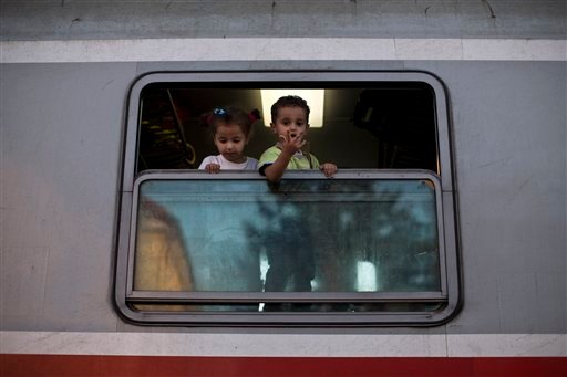 Children peer out of a window after they boarded a train close to Croatia's border with Serbia, in Tovarnik, Croatia, Monday, Sept. 21, 2015. Croatia has been under extreme pressure since thousands of asylum seekers got stuck there after Hungary shut its