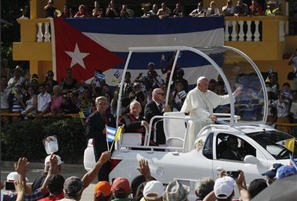 Pope Francis waves from his popemobile as travels to the Plaza of the Revolution to celebrate Mass in Holguin, Cuba, Monday, Sept. 21, 2015. Francis is the first pope to visit Holguin, Cuba's third-largest city. (Enrique De La Osa/Pool via AP)
