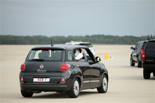 Pope Francis waves from a Fiat 500 as his motorcade departs from Andrews Air Force Base, Md., Tuesday, Sept. 22, 2015, where President and Mrs. Obama welcomed him. (AP Photo/Andrew Harnik)