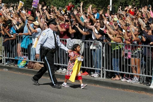 Sophie Cruz, 5, from suburban Los Angeles, is escorted back to the barricade by a uniformed U.S. Park Police officer, right before Pope Francis called for her to be brought to him for a blessing, during a parade in Washington, Wednesday, Sept. 23, 2015. S