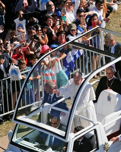 Pope Francis waves from the popemobile as he arrives for the Canonization Mass of Blessed Junipero Serra, Wednesday, Sept. 23, 2015, at the Basilica of the National Shrine of the Immaculate Conception in Washington. (AP Photo/Steve Helber)