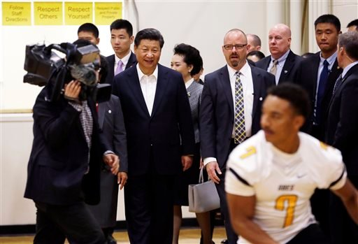 Chinese President Xi Jinping, smiles as he walks into the gym to a brief football scrimmage during a visit to Lincoln High School, Wednesday, Sept. 23, 2015, in Tacoma, Wash. Xi is on the second of a three-day trip to Seattle before traveling to Washingto