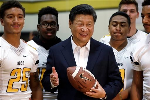 Chinese President Xi Jinping poses with football players and a football he was given during a visit to Lincoln High School, Wednesday, Sept. 23, 2015, in Tacoma, Wash. Xi is on the second of a three-day trip to Seattle before traveling to Washington, D.C.