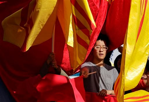 Frank Shen holds a Chinese flag to welcome Chinese President Xi Jinping as other protesters try to cover his flag with 1970's-era South Vietnam flags before a visit to Lincoln High School by the president Wednesday, Sept. 23, 2015, in Tacoma, Wash. Xi is