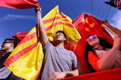 Frank Shen, left, and Chen Xiaohong holds Chinese flags to welcome Chinese President Xi Jinping as other protesters try to cover their flags with 1970's-era South Vietnam flags before a visit to Lincoln High School by the president Wednesday, Sept. 23, 20