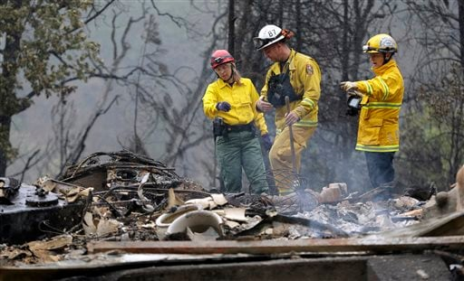 Firefighter Sean Norman, center, and search dog handlers Mary Cablk, left, and Lynne Engelbert look over the remains of a home in the Anderson Springs area of a man missing following a wildfire days earlier Wednesday, Sept. 16, 2015, near Middletown, Cali