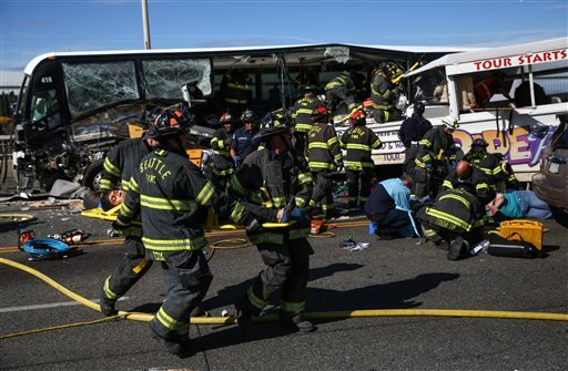 """Emergency personnel work at the scene of a fatal collision involving a charter bus, background, and a """"Ride the Ducks"""" amphibious tour bus, right, on the Aurora Bridge in Seattle on Thursday, Sept. 24, 2015. (Joshua Trujillo/seattlepi.com via AP)"""