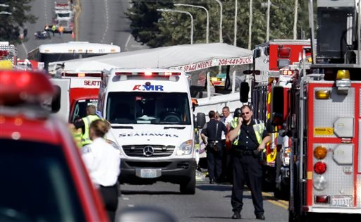"Emergency personnel work at the scene of a fatal collision involving a charter bus and a ""Ride the Ducks"" amphibious tour bus on the Aurora Bridge in Seattle on Thursday, Sept. 24, 2015. (AP Photo/Elaine Thompson)"